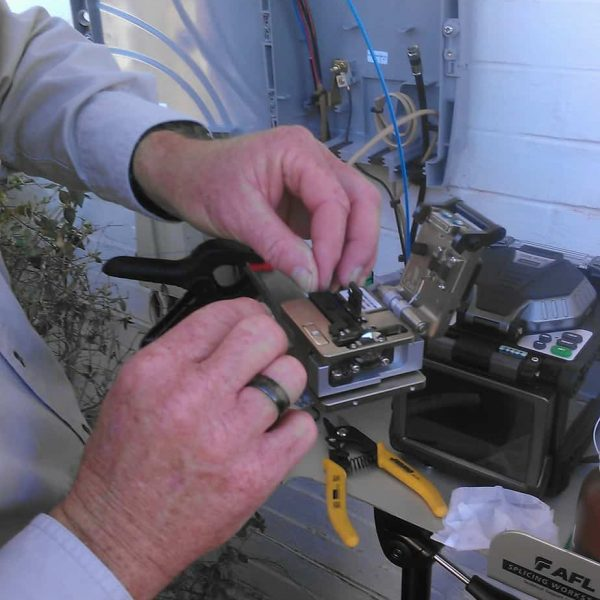 Employee Jimmy Ridgeway prepares to cleave a fiber prior to splicing it.