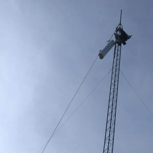 Leonard Smith pulls up the first radio and antenna to be installed on a new tower for wireless internet service.