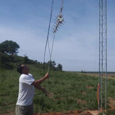 Travis Ridgeway hoists up a rope carrying a small UHF antenna.