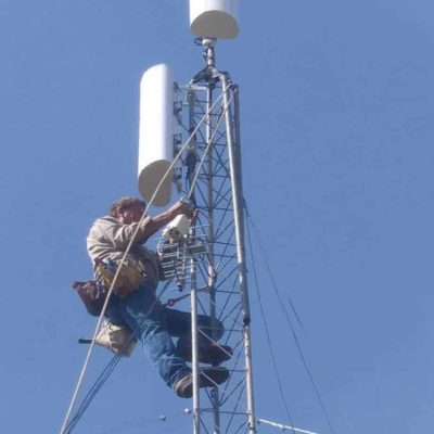 Leonard Smith climbs a tower to install a set of antennas