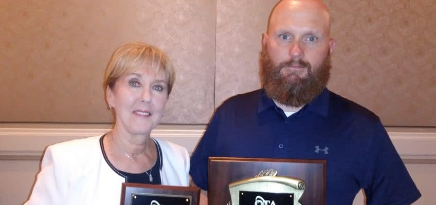 picture of Leslie Woodruff and James Powers accepting the OTA awards for Lyn Johnson and Gary Woodruff at the 2019 OTA Conference in St Louis, MO.